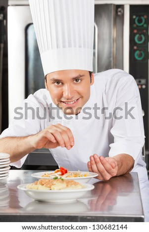 Portrait of young male chef sprinkling spices on dish in commercial kitchen