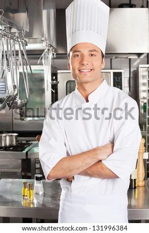 Portrait of young male chef with arms crossed in restaurant kitchen