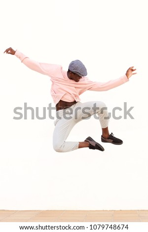 Portrait of young male dancer jumping on white background #1079748674