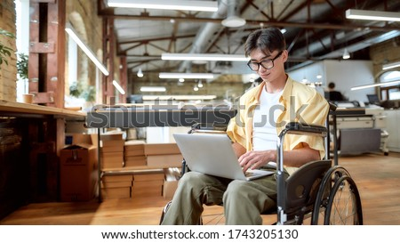 Portrait of young male office worker in a wheelchair looking at the screen of his laptop while performing in co-working space. Disability and handicap concept. Horizontal shot. Selective focus Stock foto ©