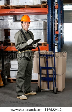 Portrait of young male supervisor writing on clipboard at warehouse