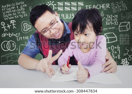 Portrait of young male teacher teach his female elementary school student to calculate with her finger in the classroom