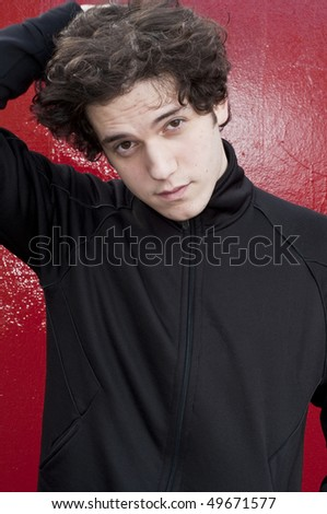 Portrait of young man against red background