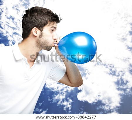 portrait of young man blowing a balloon against a cloudy sky background