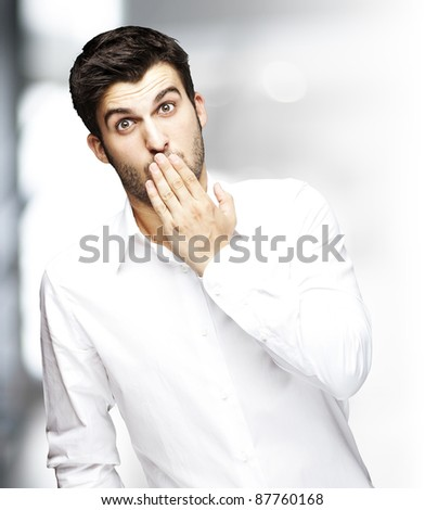 portrait of young man covering his mouth with hand indoor