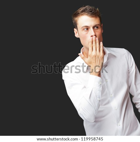 Portrait Of Young Man Covering His Mouth With Hand On Black Background