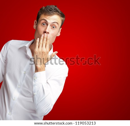 Portrait Of Young Man Covering His Mouth With Hand On Red Background