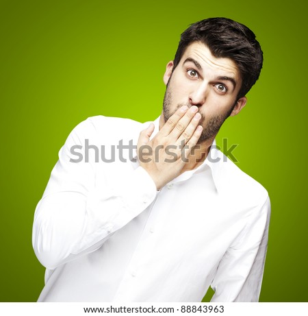 portrait of young man covering his mouth with hand over green