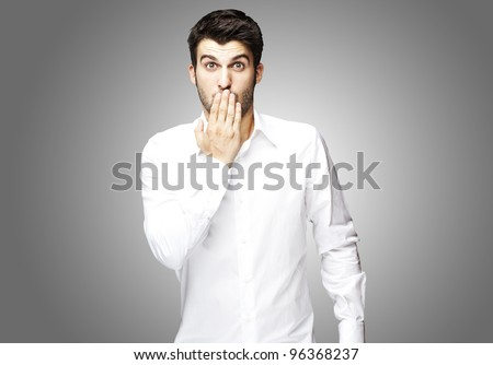portrait of young man covering his mouth with hand over grey