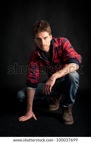 Portrait of young man crouched against black background.