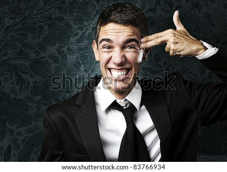 portrait of young man doing gun symbol against a grunge wall