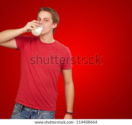 portrait of young man drinking milk over red background
