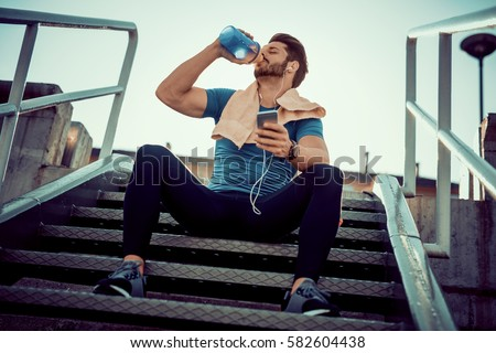 Portrait of young man drinking some water from a bottle and resting after training.