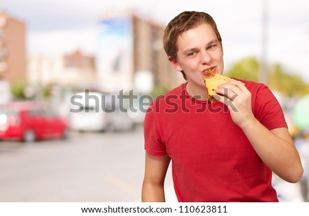 portrait of young man eating pizza at street