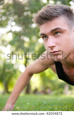 Portrait of young man full of attitude doing pushups on grass at summer park.