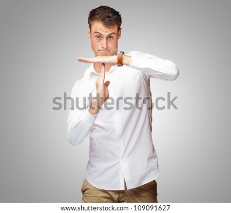 Portrait Of Young Man Gesturing Time Out Sign On Gray Background