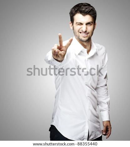 portrait of young man handsome doing good symbol over grey background