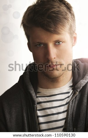 Portrait of young man handsome face and trendy clothing against modern abstract background