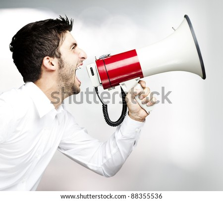 portrait of young man handsome shouting using megaphone indoor
