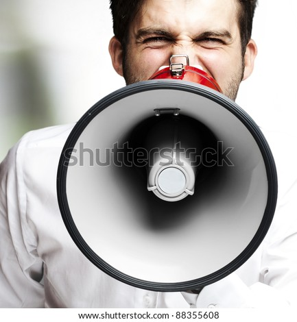 portrait of young man handsome shouting using megaphone indoor