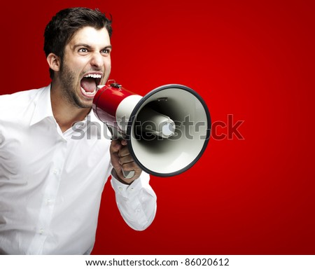 portrait of young man handsome shouting using megaphone over red background