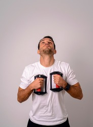 Portrait of young man having fun with push up stand hand bar using this like defibrillator