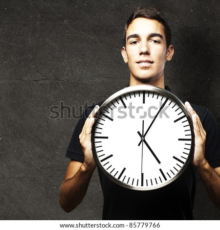 portrait of young man holding a clock against a grunge wall