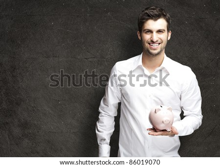 portrait of young man holding a piggy bank against a grunge background