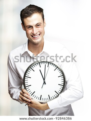 portrait of young man holding clock indoor