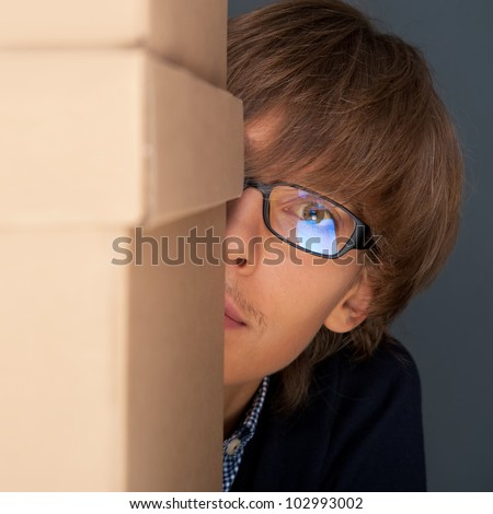 Portrait of young man holding on box against grey wall. He is starting new life