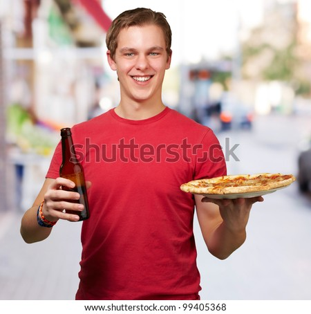 portrait of young man holding pizza and beer at street
