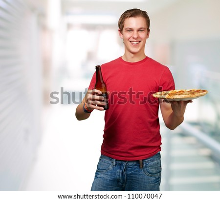 portrait of young man holding pizza and beer indoor