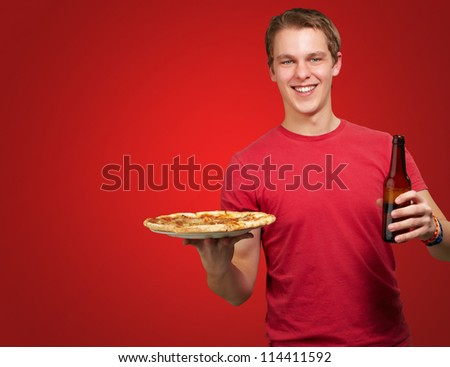 portrait of young man holding pizza and beer over red background