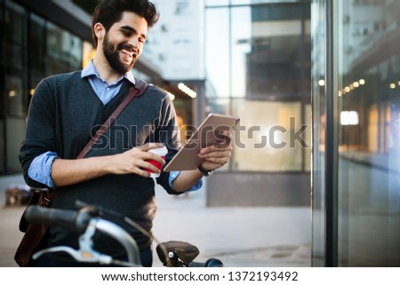 Portrait of young man holding tablet and coffee outdoor #1372193492