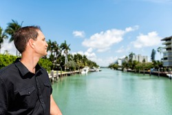 Portrait of young man in black shirt standing on bridge in Bal Harbour, Miami Florida with green ocean Biscayne Bay and residential buildings