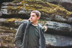 Portrait of young man in khaki parka jacket with backpack, travel adventure lifestyle