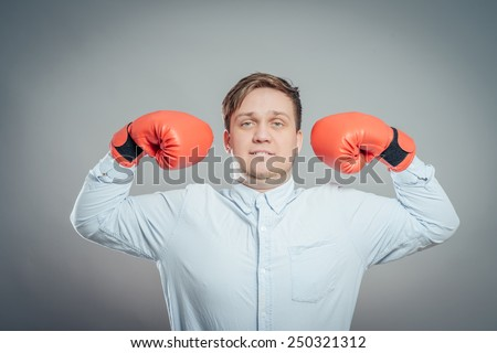 Portrait of young man in red boxing gloves fighting