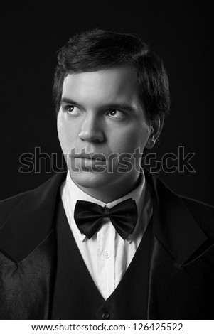 portrait of young man in tuxedo isolated on black background
