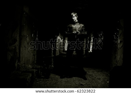 Portrait of young man inside abandoned building against vintage wall