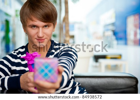 Portrait of young man inside shopping mall sitting relaxed on couch, holding box and preparing to make his couple a gift.