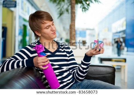 Portrait of young man inside shopping mall standing relaxed and holding gift box and bottle. He is preparing to visit his girlfriend and make a proposal