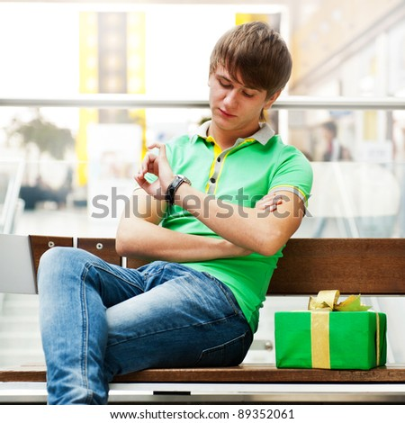 Portrait of young man inside shopping mall with gift box sitting relaxed on bench and waiting for his girlfriend