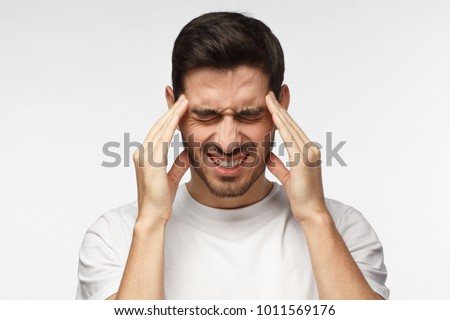 Portrait of young man isolated on grey background suffering from severe headache, pressing fingers to temples, closing eyes to relieve pain with helpless face expression