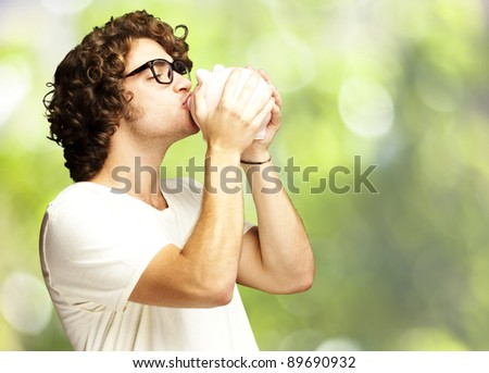 portrait of young man kissing a piggy bank against a nature background - stock photo