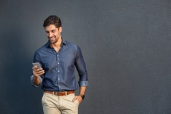 Portrait of young man leaning against a grey wall using mobile phone. Happy business man messaging with smartphone isolated on gray background with copy space. Smiling guy typing and reading a message
