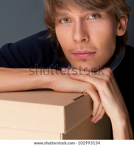 Portrait of young man leaning on box against grey wall. He is starting new life