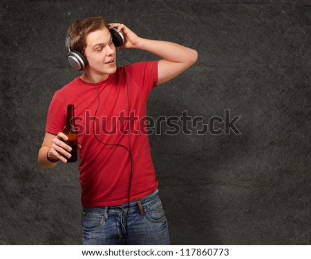 portrait of young man listening music and holding beer against a grunge wall - stock photo