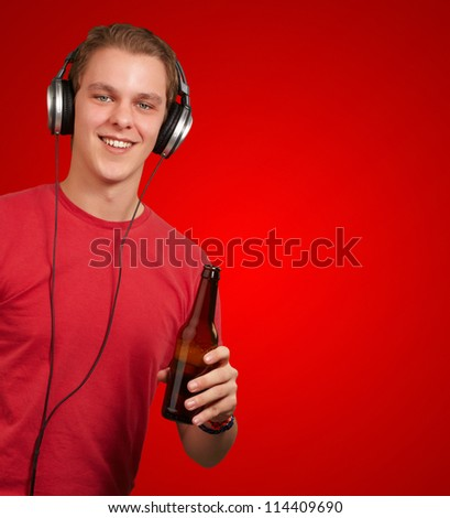 portrait of young man listening music and holding beer over red background