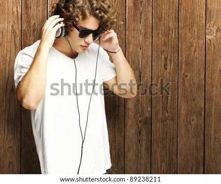 portrait of young man listening to music against a wooden wall
