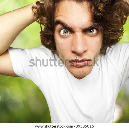 portrait of young man looking confused against a nature background